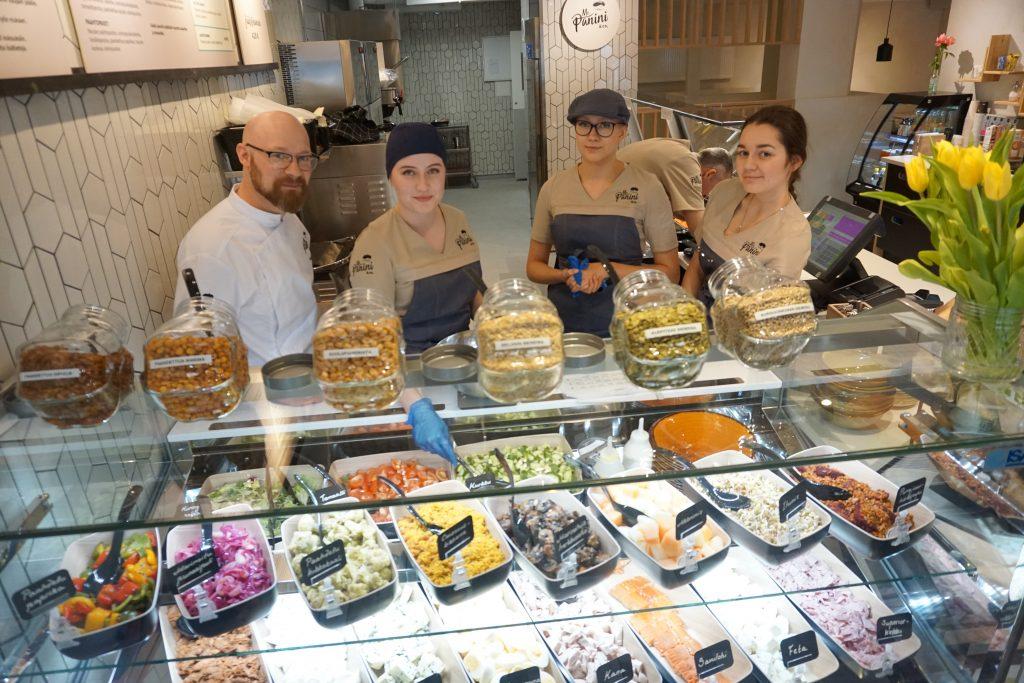 Tampere saa Snellman-konsernin kaikkien aikojen ensimmäisen Mr. Panini & Co. -pikaruokaravintolan, joka avaa ovensa perjantaina 26. huhtikuuta Hämeenkatu 3:ssa. Keittiömestari Tommi Pylkkänen (vas.) opasti torstaina kahvilatyöntekijöitä rakentamaan salaattiannoksia ja valmistamaan paniineja. (Kuva: Matti Pulkkinen)